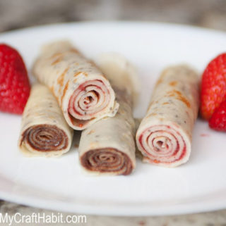 Crepes rolled with jam and nutella stacked on a white plate, surrounded by fresh strawberries