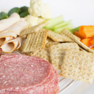 Cold cuts, crackers and fresh vegetables on a white plate