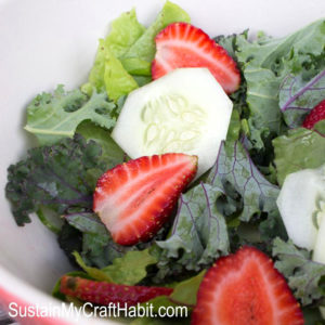 Salad bowl filled with slices cucumbers, strawberries, kale and greens.
