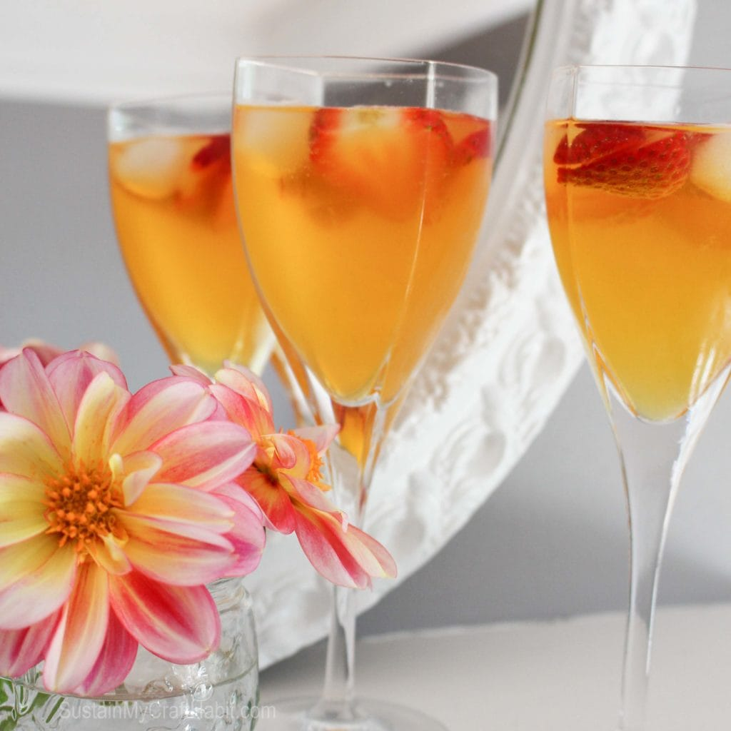 A stemmed wine glass filled with the peach belini and garnished with fresh strawberry slices