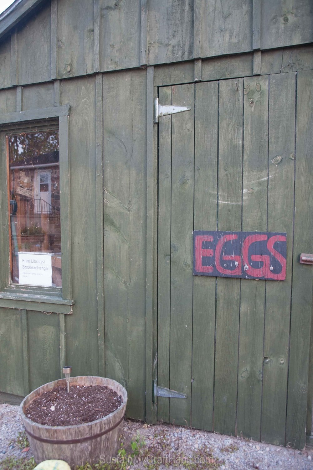 A rustic gray wood shack with a sign on the front reading eggs,