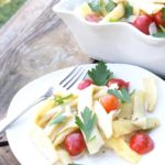 A white plate filled with yellow pole bean salad on a rustic wood surface