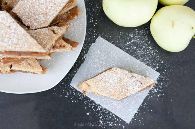 An overhead view of a diamond shaped piece of apple pita pie, sprinkled with icing sugar and place on a piece of parchment paper.