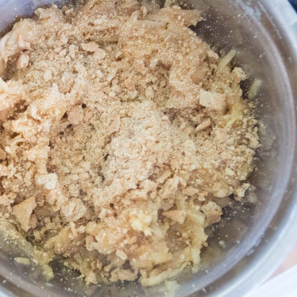 Cookie crumbs being combined into the sauteed cinnamon apple mixture