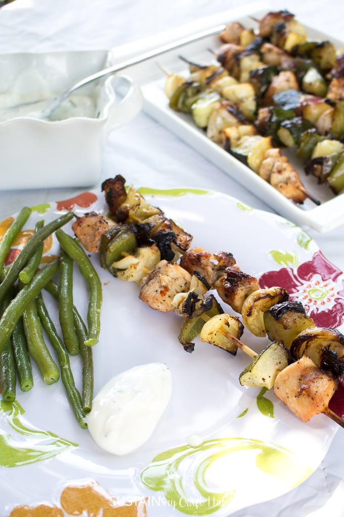 Plate filled with grilled chicken shish kabob recipe, sauteed green beans, and creamy dill dipping sauce
