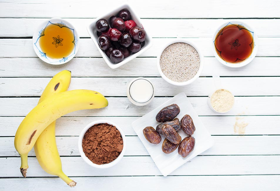 Ingredients to make a vegan chcoloate cherry bowl smoothie laid out on a white plank surface. Includes bananas, cherries, majool dates and seeds.
