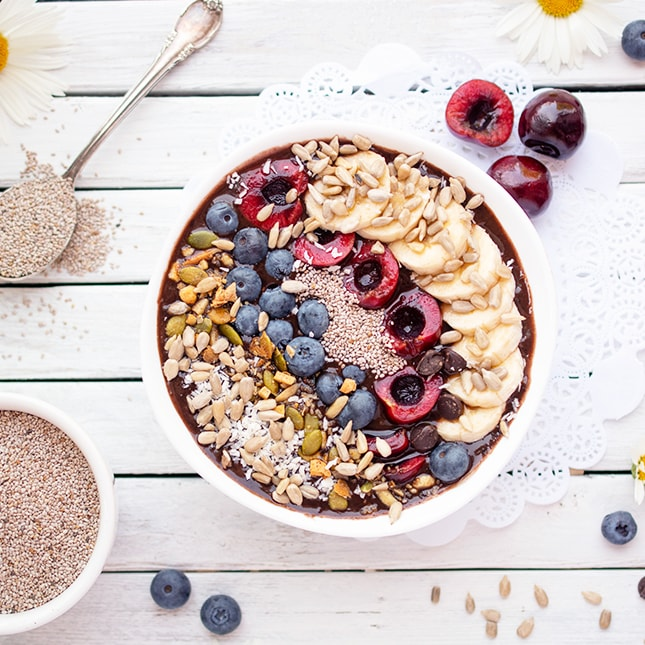 A large bowl filled with vegan chocolate cherry smoothie, topped with cherries, blueberries, chia seeds and sliced bananas