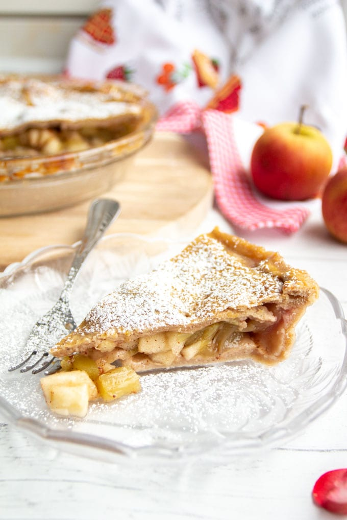 A slice of cinnamon apple rhubarb pie sprinkled with powdered sugar on a glass dessert plate with apples and pie in the background.
