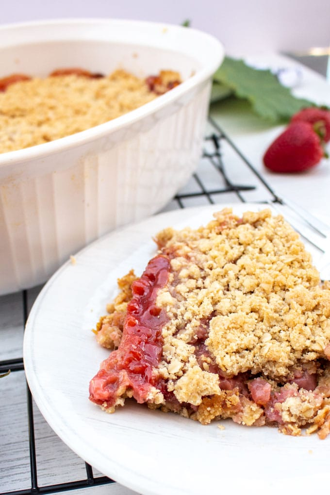 A piece of baked strawberry rhubarb crisp on a white plate on a black cooling tray.
