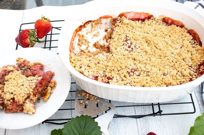 A white Corningware dish filled with baked strawberry and rhubarb crisp. On large piece has been taken out and put on a white plate. Fresh strawberries surround the dishes.