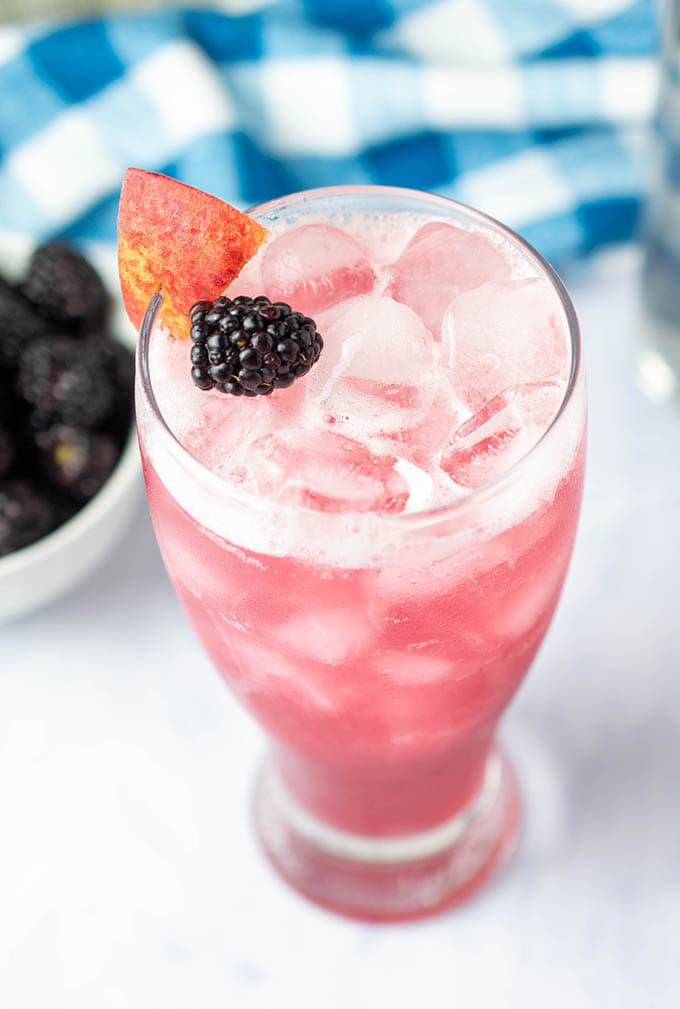 A peach blackberry vodka cocktail in a tall clear glass, garnished with a fresh blackberry and peach wedge. A blue checkered napkin and small bowl of blackberries are in the background.