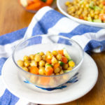 A glass bowl filled with chickpea, carrot and cucumber salad.