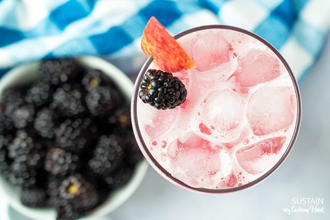 Overhead view of the blackberry cocktail in a clear glass, filled with ice and garnished with fresh peaches and blackberries.