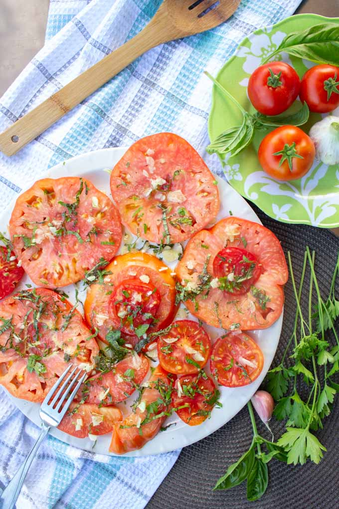 An overhead image of a round white platter covered with a sliced tomatoes salad. A blue checkered tea towel rests underneath the plate.