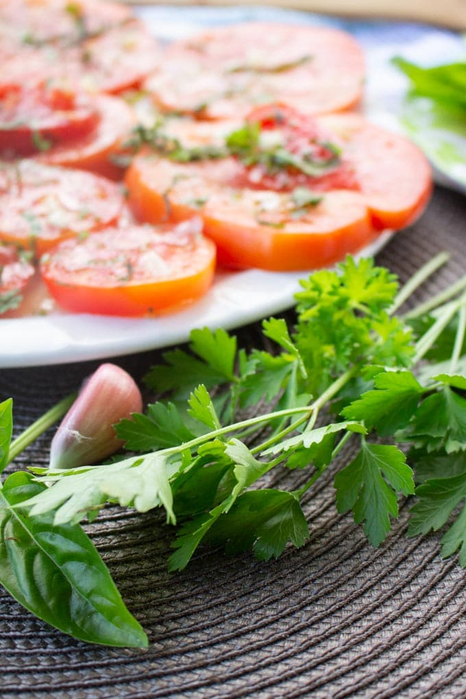 Close up image of parsley, basil and a clove of garlic. A plate of sliced tomatoes salad is seen in the background.