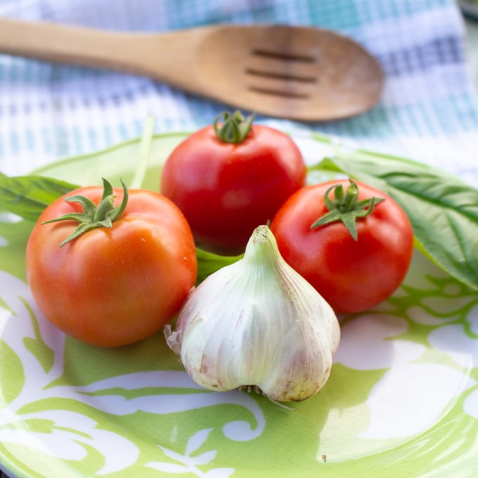 Close up image of three red tomatoes and a head of garlic on a green plate. A wooden spoon rests in the background.