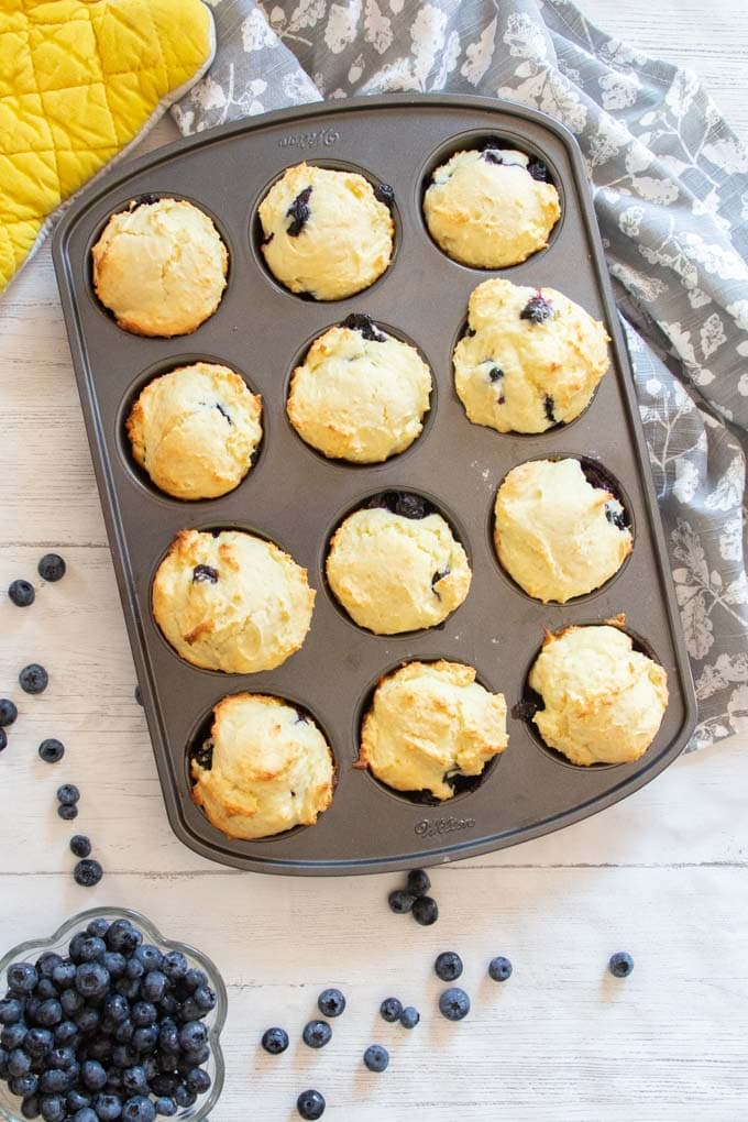 Overhead image of a muffin tin filled with baked blueberry muffins.