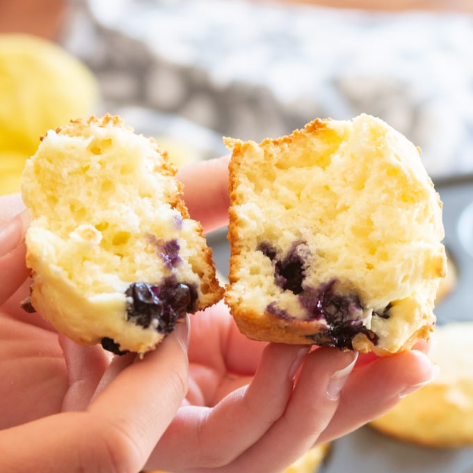 Close up image of someone holding a blueberry muffin broken in half to show the inside.