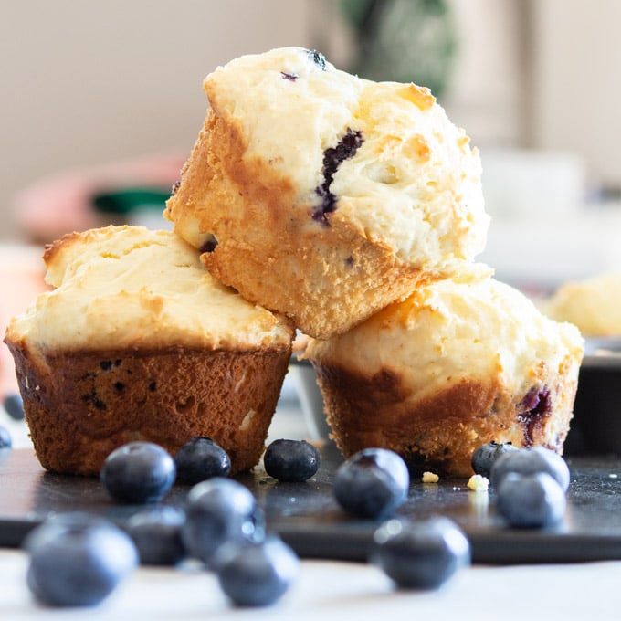 Stack of baked muffins surrounded by fresh blueberries.
