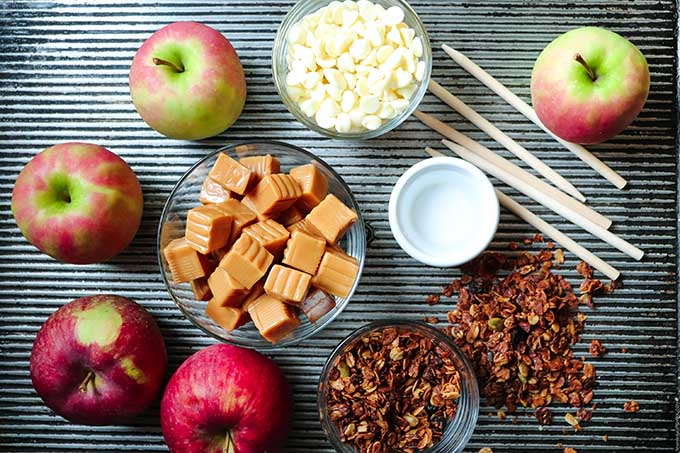 An overhead view of supplies needed to make the granola-dipped caramel apples recipe. Includes apples and small clear bowls filled caramels, white chocolate and granola on a dark grey surface.
