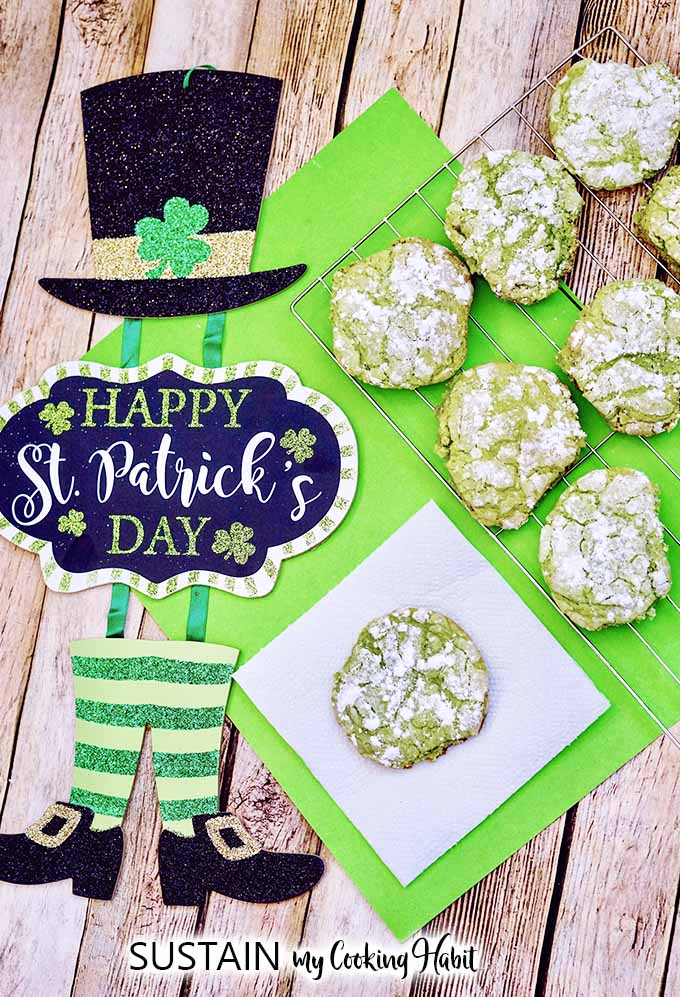 Finished and baked green crinkle cookies cooling on a cooling rack on a bright green place mat and rustic wood surface. A decorative sign reading Happy St. Patrick's Day is placed beside the cookies.