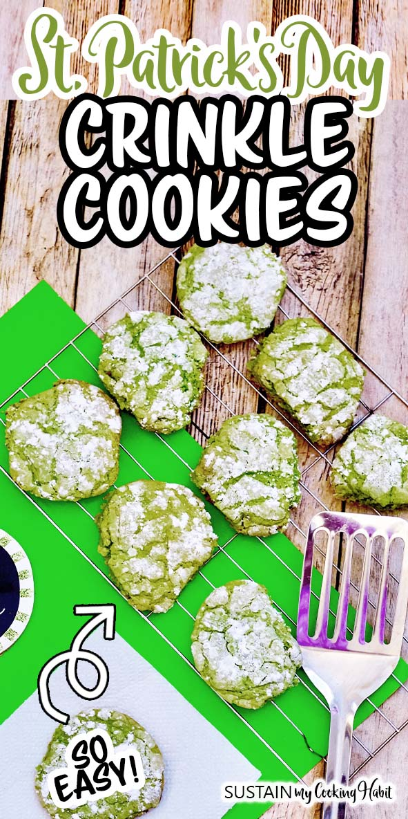 A batch of green crinkle cookies on a cooling rack on a bright green place mat and rustic wood surface.  A silver spatula rests on the side and text overlay reads St. Patrick's Day Crinkle Cookies.