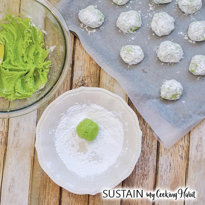 A round green ball of dough being rolled in a place filled with powdered sugar. A cookie sheet filled with cookies ready to be baked is beside the plate.