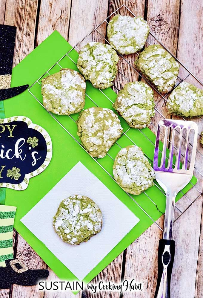 A batch of green crinkle cookies cooling on a cooling rack on a bright green placemat and rustic wood surface.