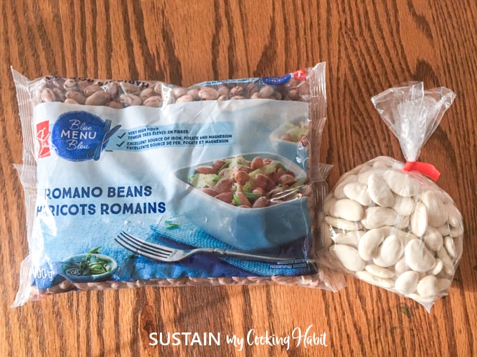 Two bags filled with dried romano beans and dried white lima beans on a wood surface.