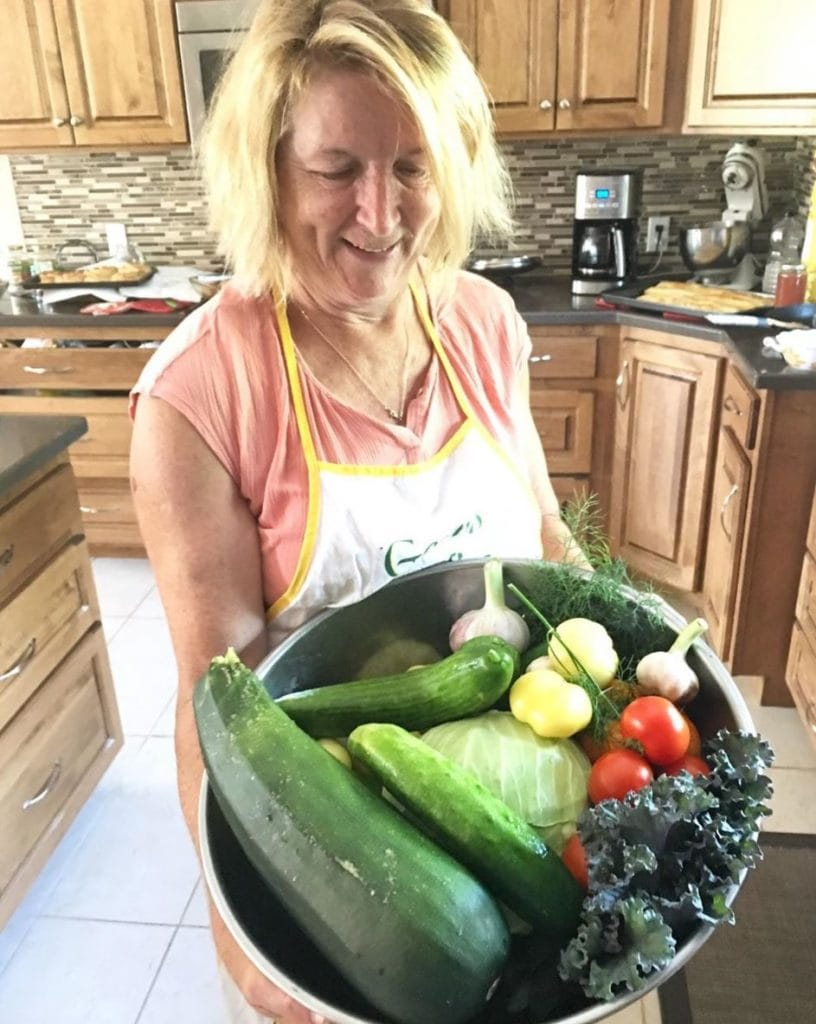 Woman holding a large silver bowl filled with cucumbers, tomatoes, kale, zuchinni and other vegetables.