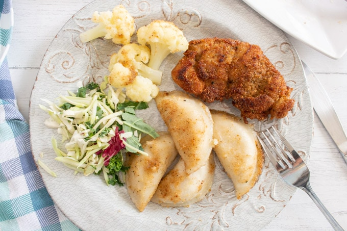 Overhead view of a round plate with perogis, breaded chicken, cauliflower and coleslaw.