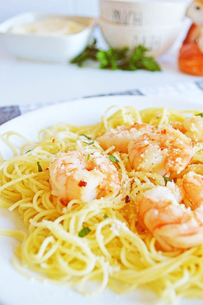 Close-up image of finished shrimp scampi on a white plate. Cooked shrimp is placed on a bed of spaghettini.