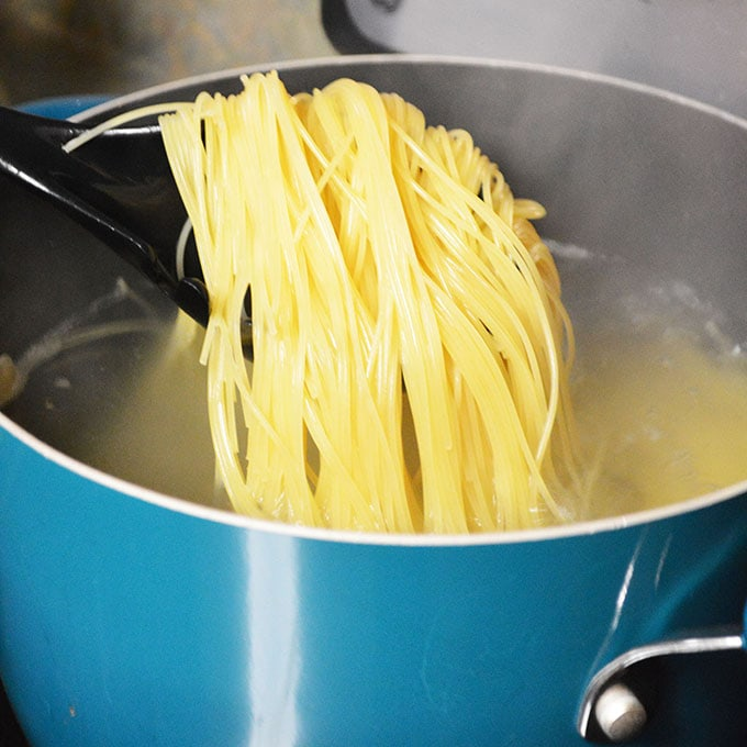 Spaghetinni pasta pulled out of a blue pot of boiling water with a black spoon.