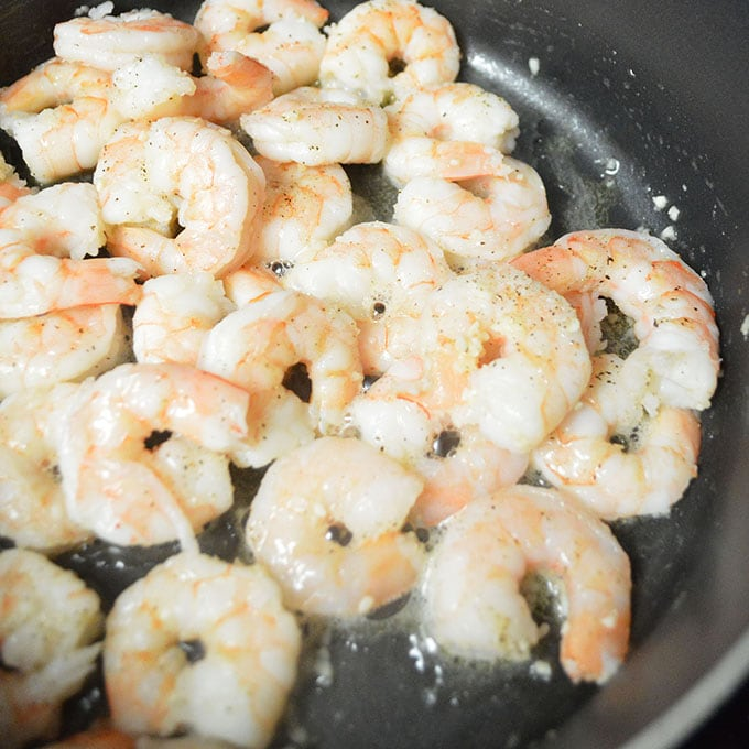 Shrimp being cooked inside of a frying pan.