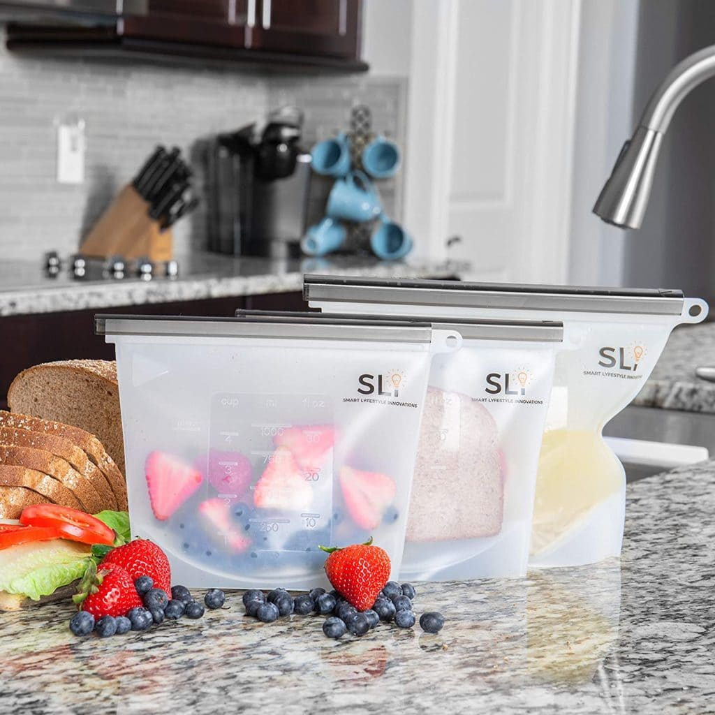 Three silicone food bags placed on a kitchen counter and filled with fruit, a sandwich and soup.