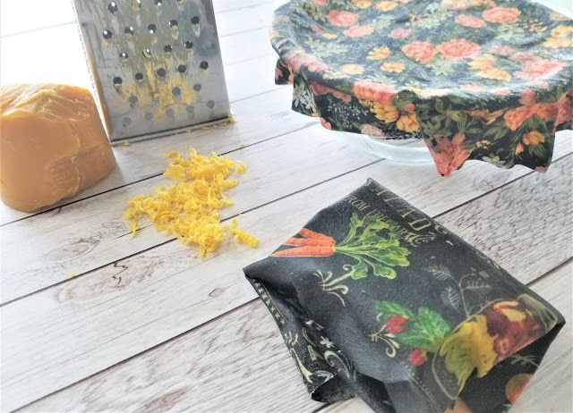 Materials needed to make a sustainable beeswax wrap, including a cheese grater, beeswax and fabric.