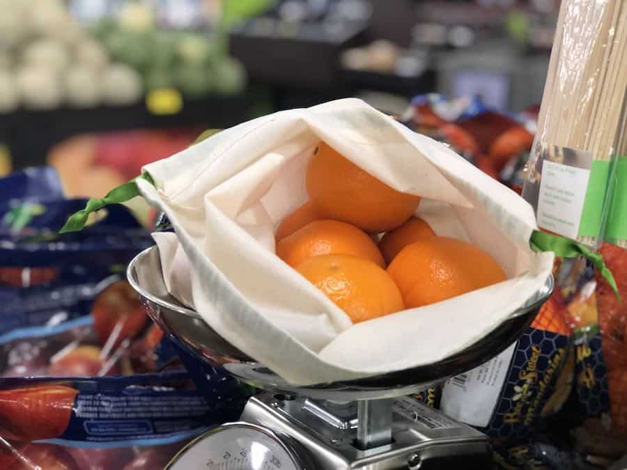 An open cloth produce bag with oranges inside.