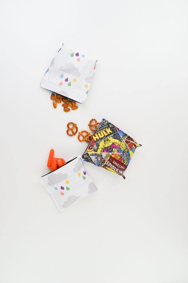 Reusable snack pouches with character designs holding almonds, pretzels and carrots.