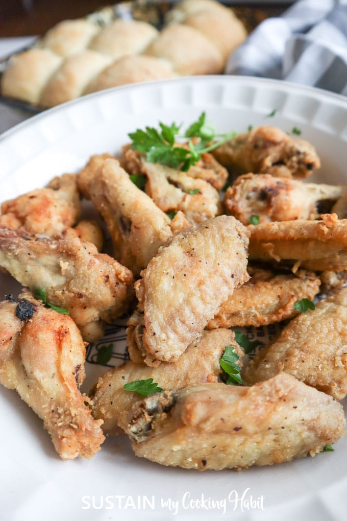 Cooked home Style chicken wings on a plate with garnish.