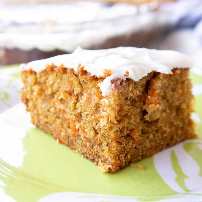 slice of delicious and moist carrot cake with cream cheese frosting