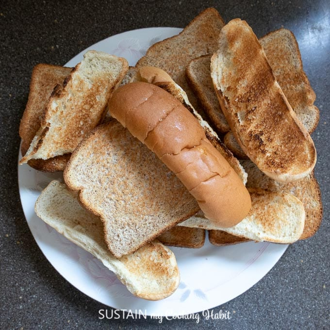 A plate filled with a variety of dried and stale breads including hot dog buns and sandwich bread.