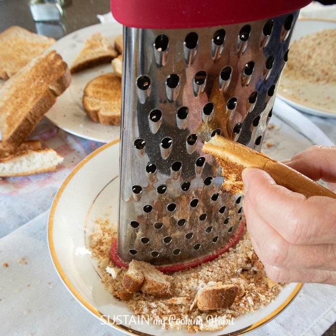 Using a cheese grater to make breadcrumbs.