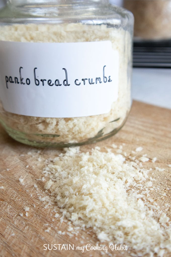 Close up image of Panko breadcrumbs with a labelled glass jar filled with bread crumbs in the background.