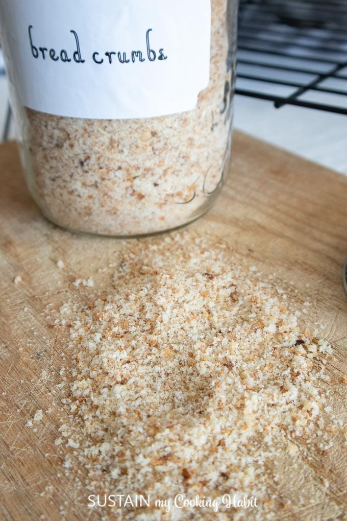 Close up image of homemade breadcrumbs on a wood cutting board surface. A labelled glass jar filled with bread crumbs is in the background.