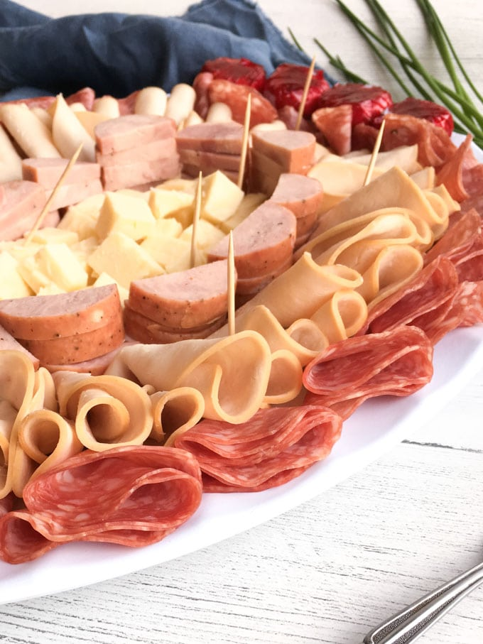 Close up of deli cold cuts and cheese on a serving plate with tooth picks.