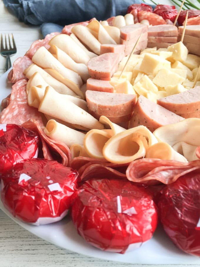 Close up of baby bell cheese placed around the edge of the serving tray alongside deli cold cuts and cheese.