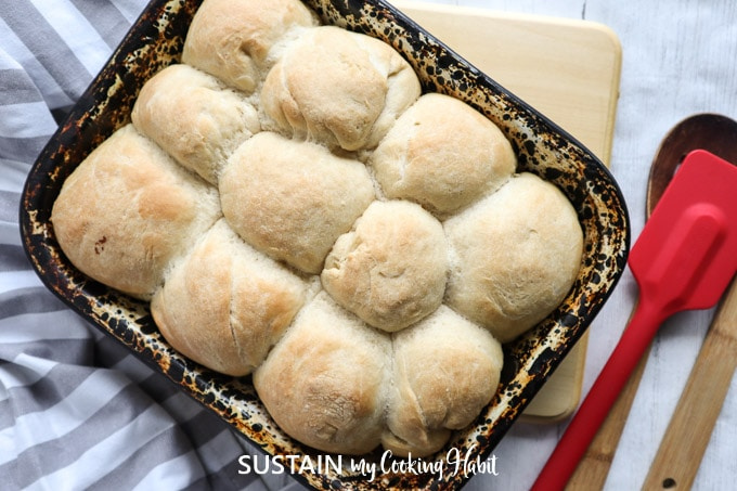 Overhead view of baked dinner rolls in a deep dish, placed next to a  cloth, spatula, cutting board and wooden spoon.