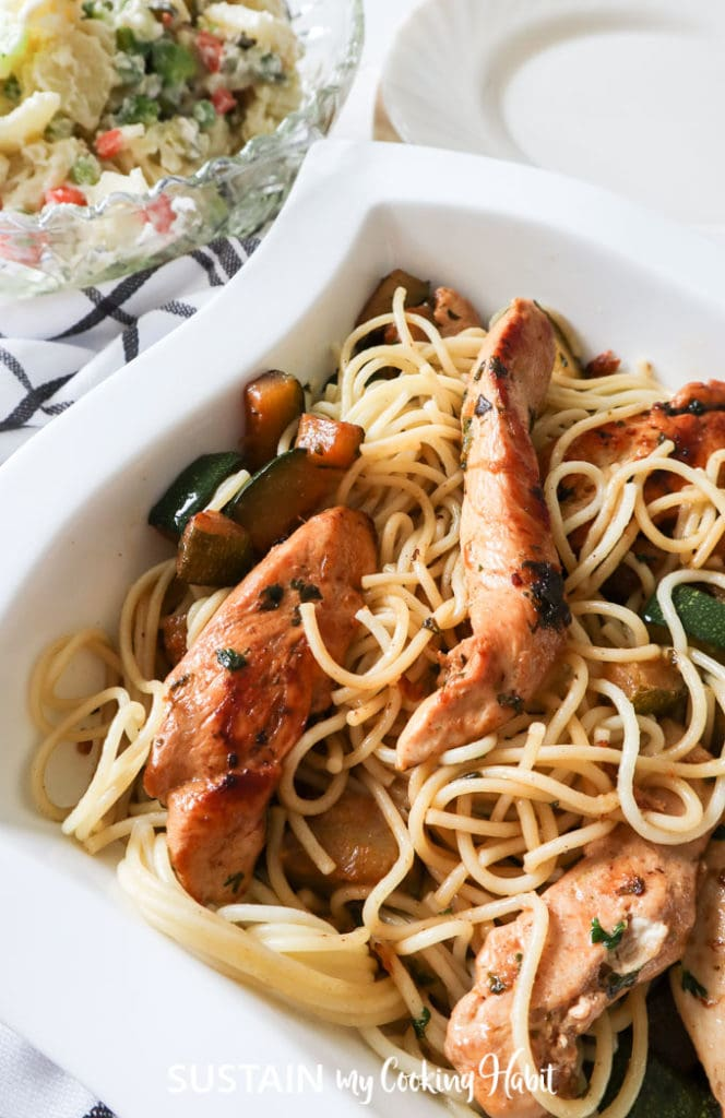 Chicken zucchini pasta meal served in a white dish.