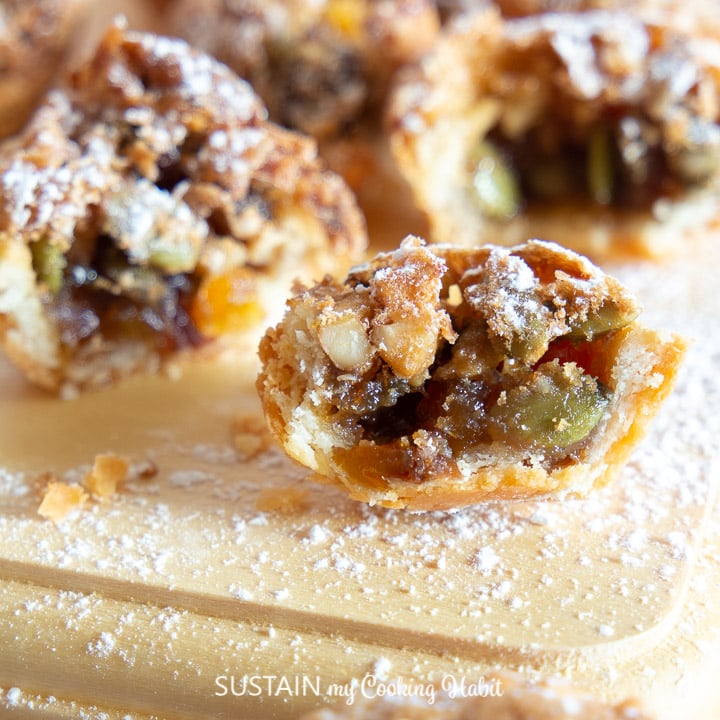 one apricot and pecan tassie cut in half to show the tasty filling