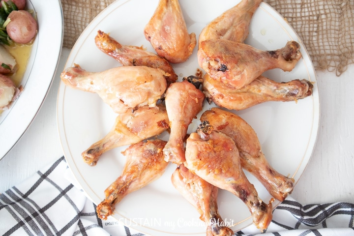 Overhead view of a plate of baked drumsticks